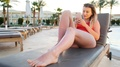 Attractive Sexy Woman In Red Bikini Lying On Deck Chair Using A Smartphone App